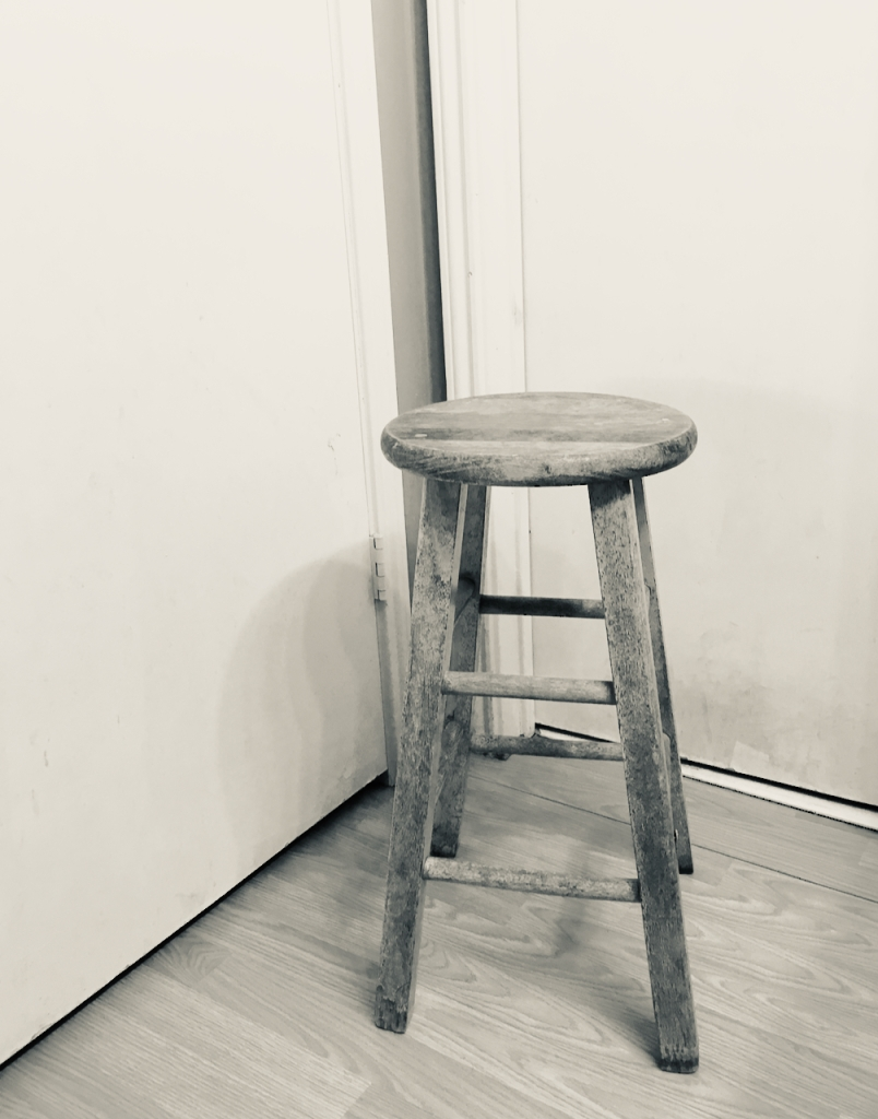 An empty stool in a corner